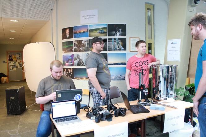 Joakim Tetlie (t.v.) fra fotoklubben studerer kamerautstyret, mens Christian Jenssen (midten) og Hogne Andersen snakker med en potensiell ølbrygger. Foto: Benedicte S. Larsen
