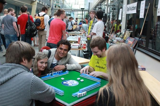 Martin Hansen (i gult) viser fram Mahjong til interesserte studenter. Foto: Benedicte S. Larsen
